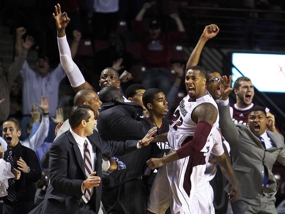 Sampson Carter (right) touches off the celebration on the UMass bench as his last-second shot drops for a season-opening victory.