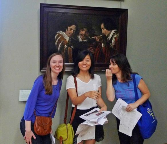 "Treasure hunters (from left) Tara Byrne, Wan Yan, and Susan Feess finding Simon de Vos's ""Gathering of Smokers and Drinkers."""