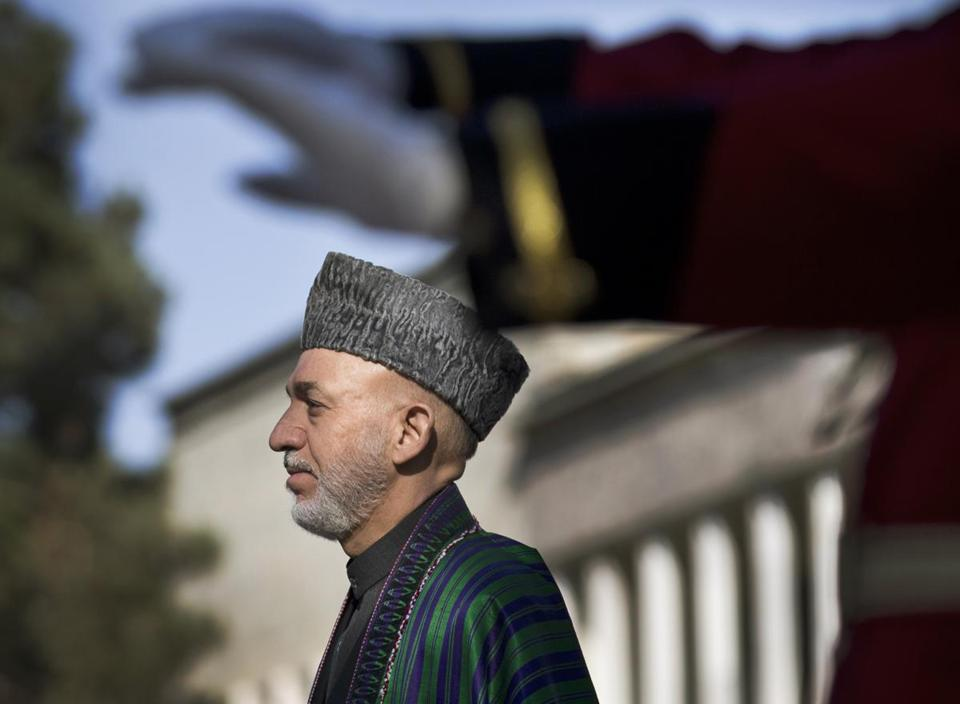 In this Friday, Oct. 26, 2012 file photo, Afghan President Hamid Karzai reviews the guard of honor during the first day of Eid al-Adha celebrations at the palace in Kabul, Afghanistan. Karzai accuses U.S. forces of capturing and holding Afghans in violation of an agreement to turn over that responsibility to the Afghans. (AP Photo/Anja Niedringhaus, File)