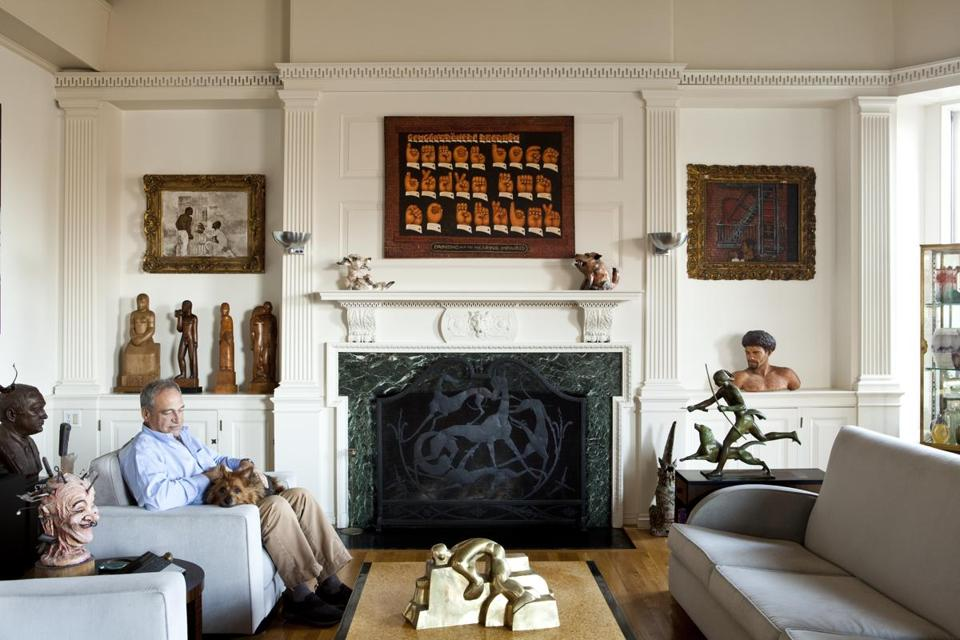 "Retired attorney John Axelrod with his collection of so-called ""Loisaida"" art; above and flanking the fireplace, three paintings by Martin Wong. The sculptures represent a mix of 20th century American styles."