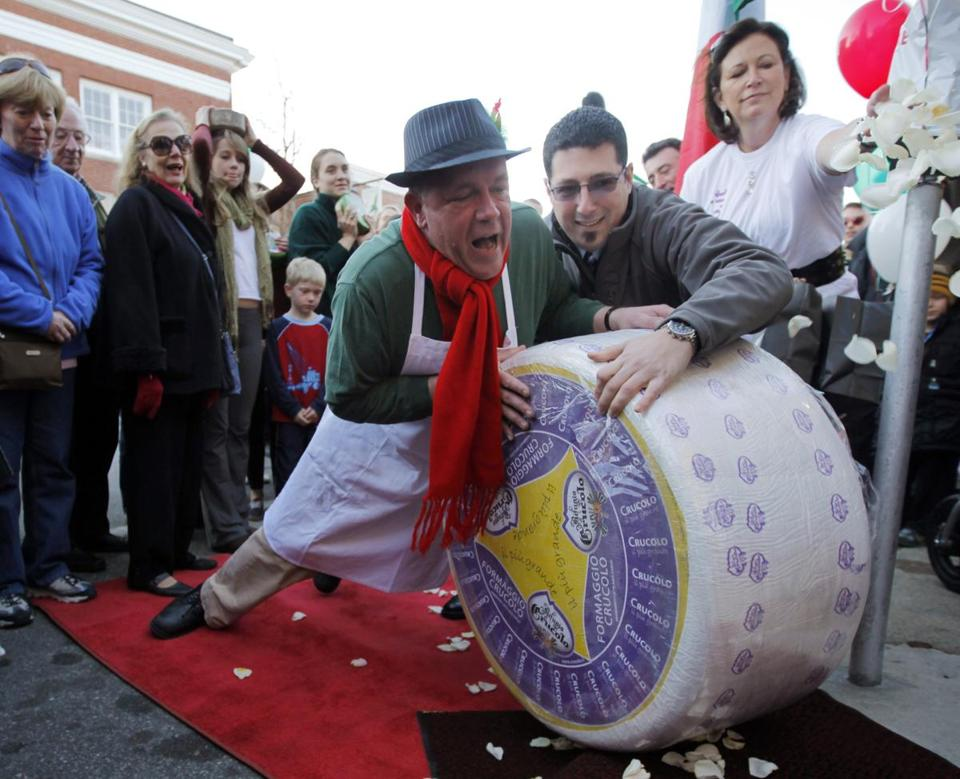 Peter Lovis, proprietor of the Concord Cheese Shop, and Francesco Gallo, pushed a 400-pound wheel of Crucolo cheese over the curb down a red carpet in the street to the shop in Concord, Massachusetts.