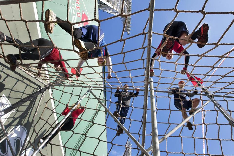 Aja Varney, Christine Fried, and Eric Tobin, scaling cargo netting in front of the Green Monster as part of the 2.5-mile Spartan Race at Fenway Park.