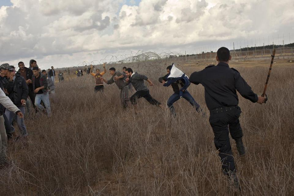 AHamas police officer turned some Palestinians back near the border in southern Gaza Strip on Friday as crowds surged toward the fence.