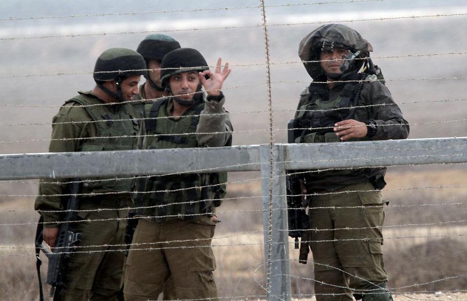 Israeli soldiers keep watch as Palestinian youths demonstrate next to the security fence standing on the Gaza border with Israel.
