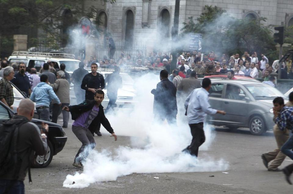 Protesters ran from tear gas released by police Saturday during clashes in front of the Supreme Judicial Council in Cairo.