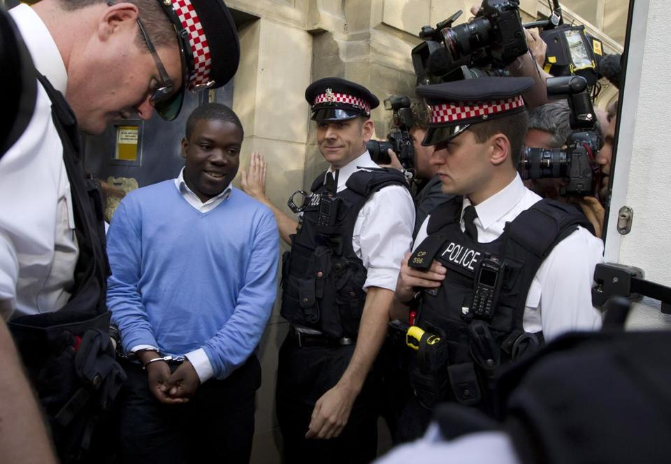 Former UBS trader Kweku Adoboli was flanked by police after a court appearance in London in 2011.