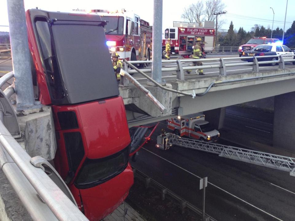 Rescue workers assessed their strategy for removing the driver of a pickup left hanging from an overpass Saturday.