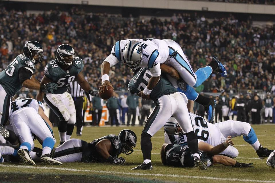 Panthers QB Cam Newton hurdles Eagles safety Nate Allen to score in the third quarter.