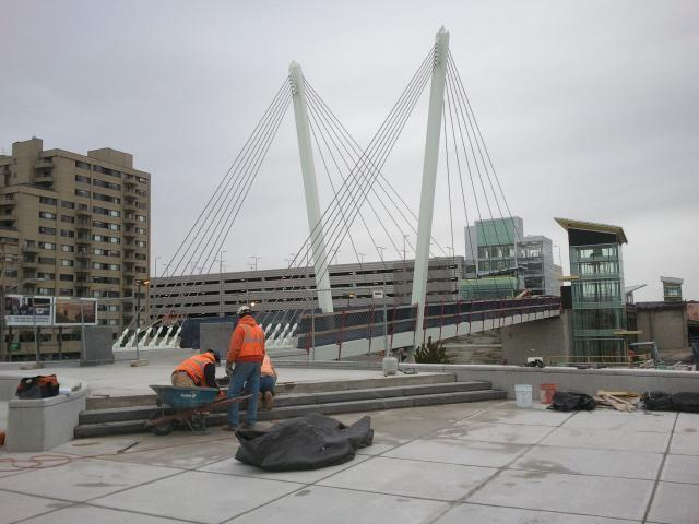 A crew works on the plaza at the pedestrian bridge, which was named for Christina and John Markey.