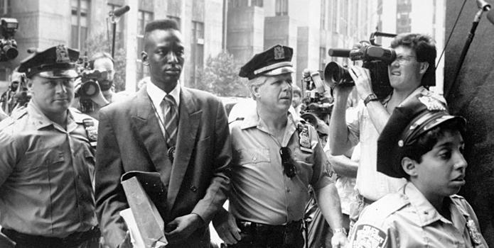 "Yusef Salaam is escorted by police in New York in 1990 in a scene from Ken Burns's documentary ""The Central Park Five."""