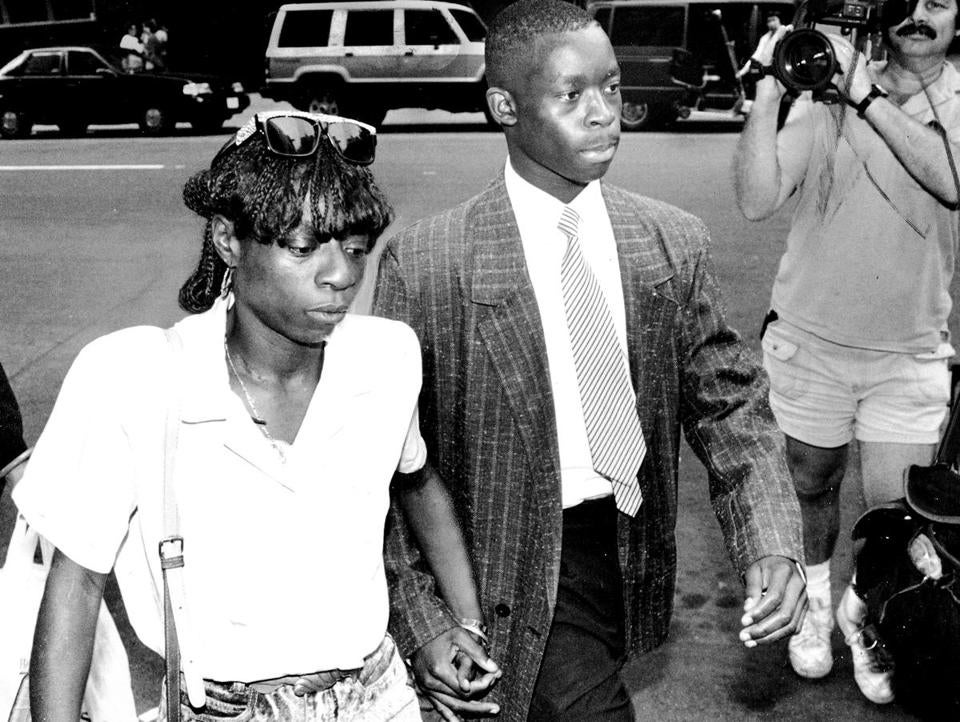 Antron McCray, one of the suspects in a 1989 rape of a woman in Central Park, walks to the courthouse with his mother, Linda.