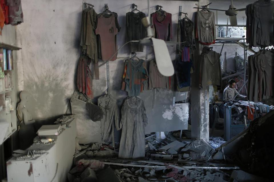 A Palestinian in Gaza arranged clothes at his shop, which witnesses said was damaged in an Israeli air strike.