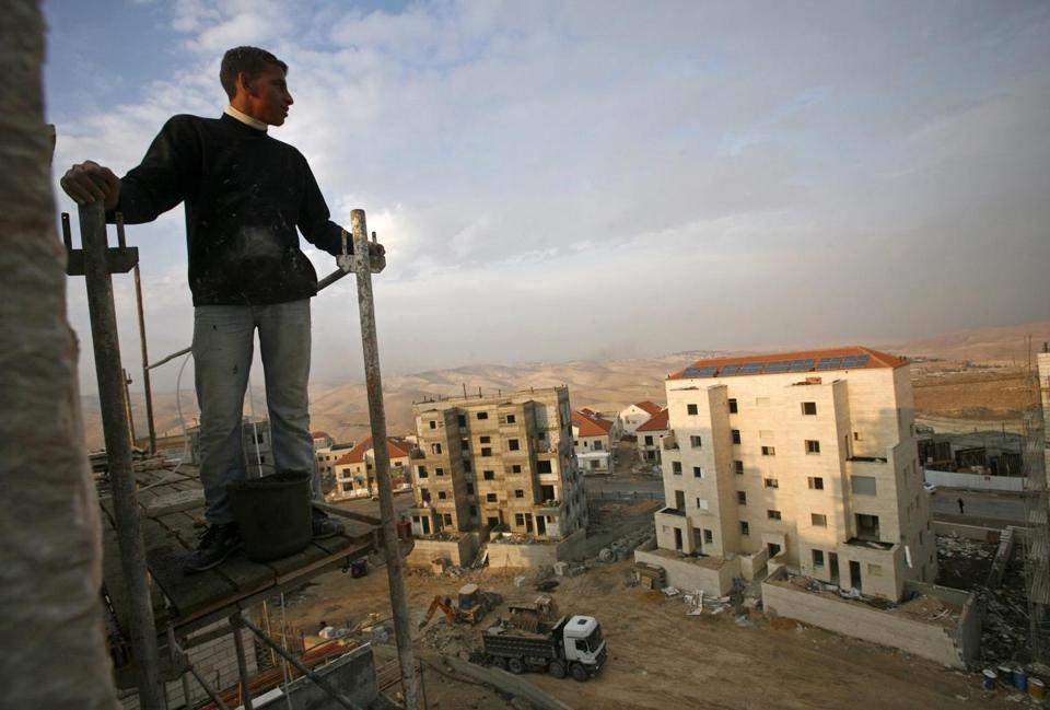 A Palestinian laborer at a construction site in the West Bank Jewish settlement of Maale Adumim. Israel plans to build homes in the occupied West Bank and East Jerusalem.