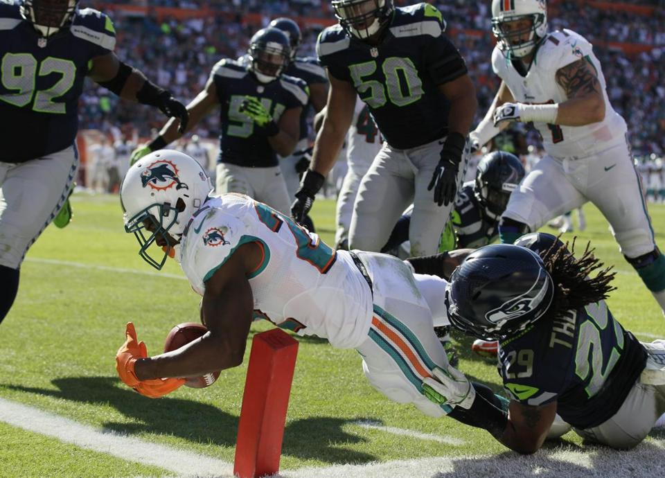 Miami Dolphins running back Reggie Bush stretched for a touchdown Sunday, Nov. 25, 2012 in Miami.