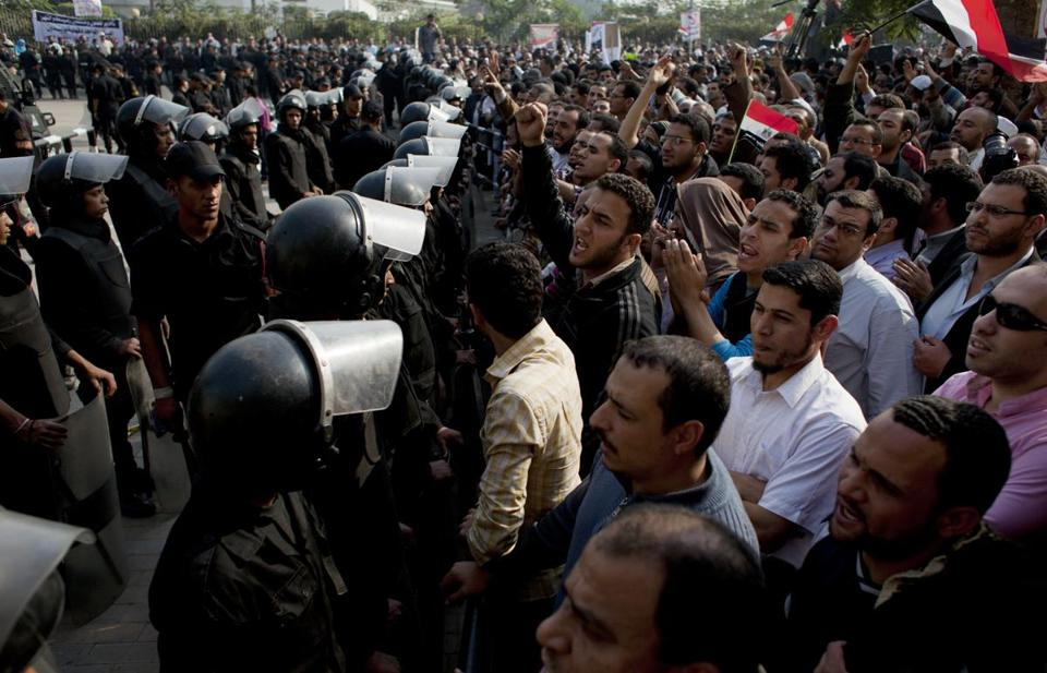 Supporters of Egyptian President Mohammed Morsi chanted slogans as riot police stood guard in front of the entrance of Egypt's top court, in Cairo, Sunday.