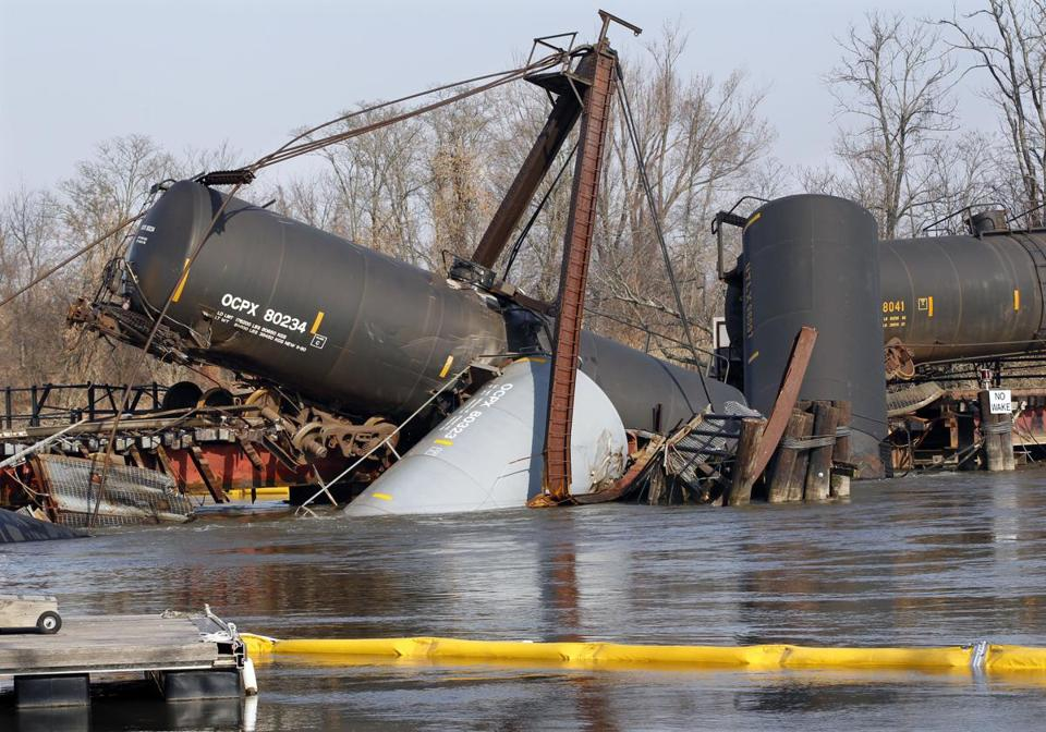 A containment boom floated in Mantua Creek Saturday, near freight train tank cars that derailed on Friday.