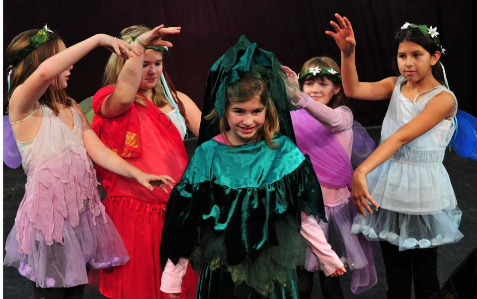 "Ella de Gaspe Beaubien (center) plays a Christmas tree in ""Holiday Delights"" at Gloucester Stage."