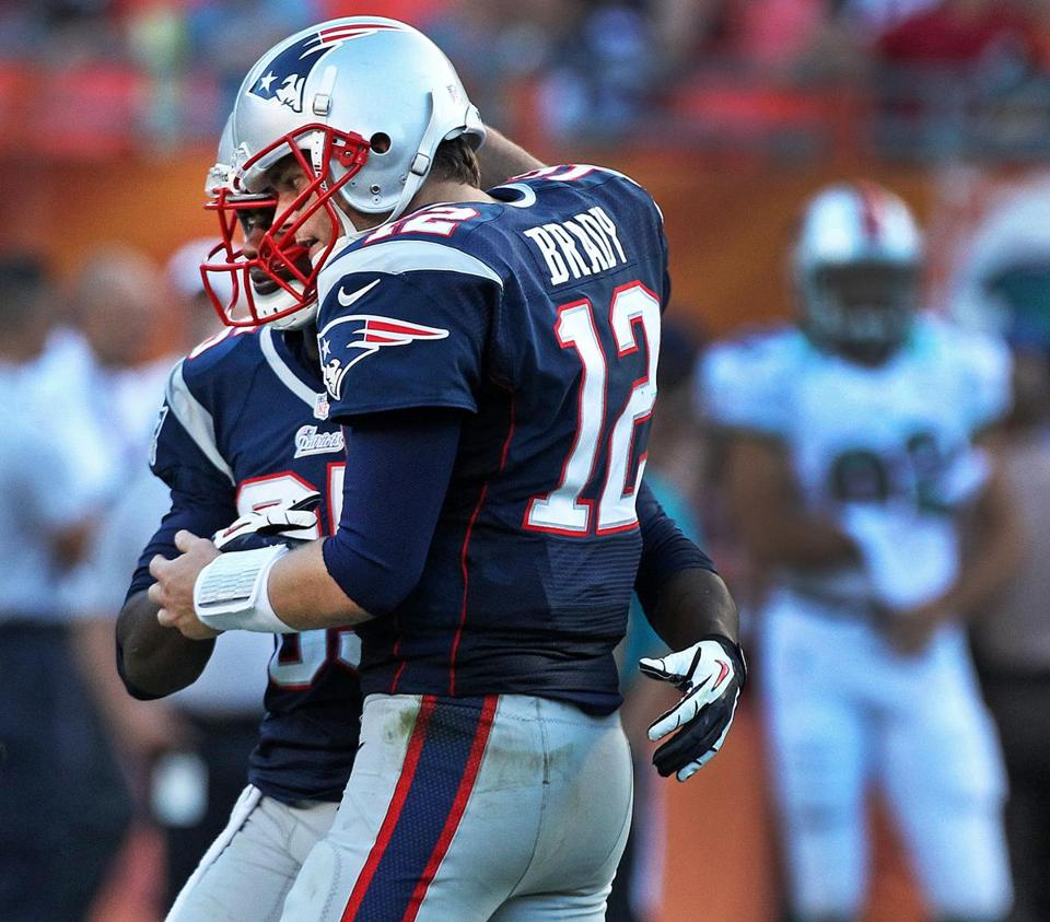Tom Brady congratulates Brandon Lloyd for a kick recovery; the QB and WR connected only once Sunday.
