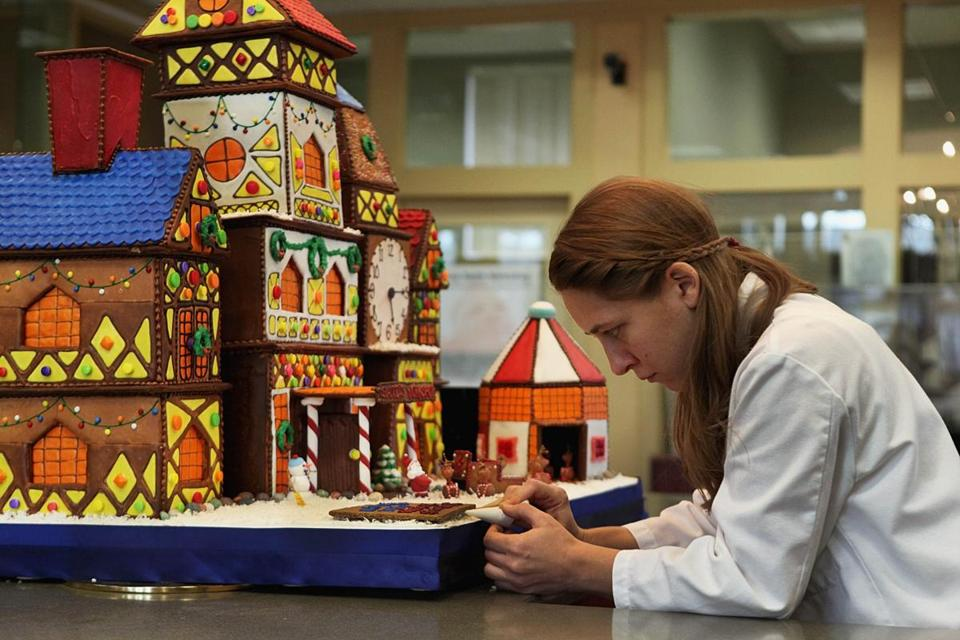 Kristen Coniaris put the finishing touches on a gingerbread house on display at The Cooperative Bank in Charlestown.
