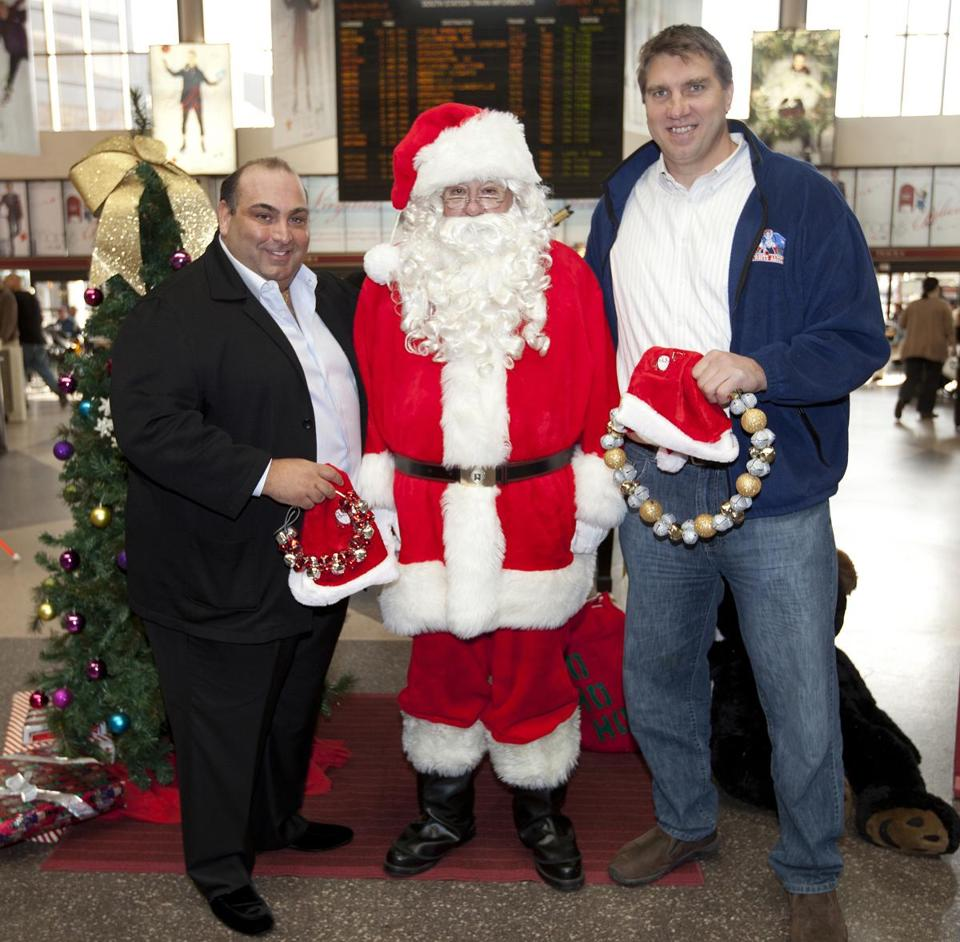 Nick Varano (left), owner of North End restaurants Strega and Nick Varano's Famous Deli, and former New England Patriots offensive tackle Max Lane helped Globe Santa with his fund Wednesday at South Station.