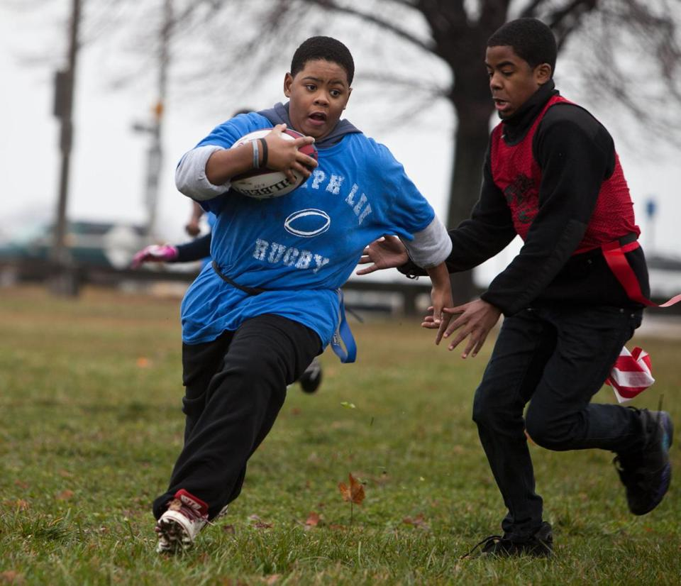 Malcom Simms runs with the ball with Michael Castro in pursuit during the Rugby middle school championships at Moakley Park earlier this month.