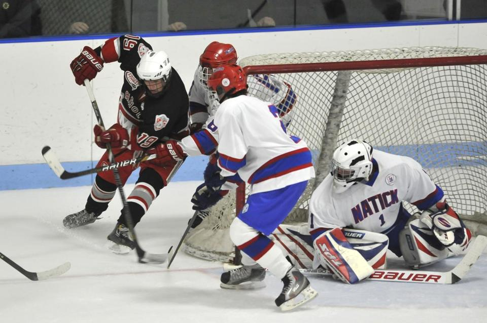 Natick goalie Mike White guards the net as Catholic Memorial's Jack O'Hear tries to force the puck past Natick's Jack O'Connor.