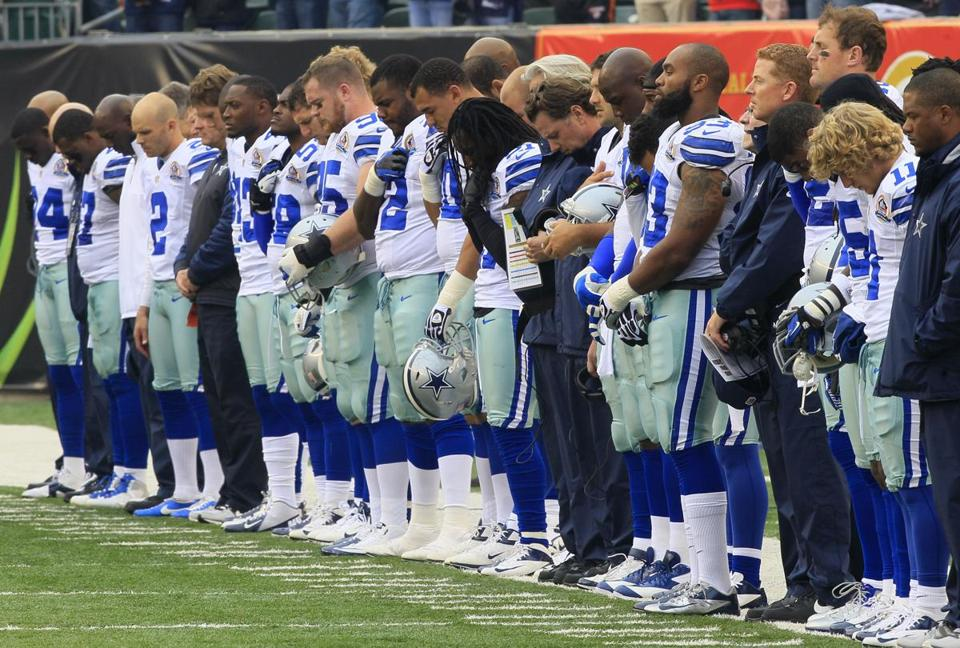 The Cowboys lower their heads during a moment of silence for teammate Jerry Brown, who died in a car crash Saturday that left another Cowboy facing manslaughter charges.