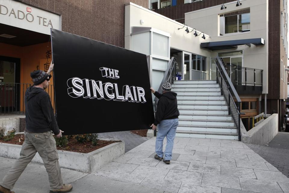 Ryan Paddy (left) and John Christian carry the sign for the new Cambridge music venue The Sinclair.