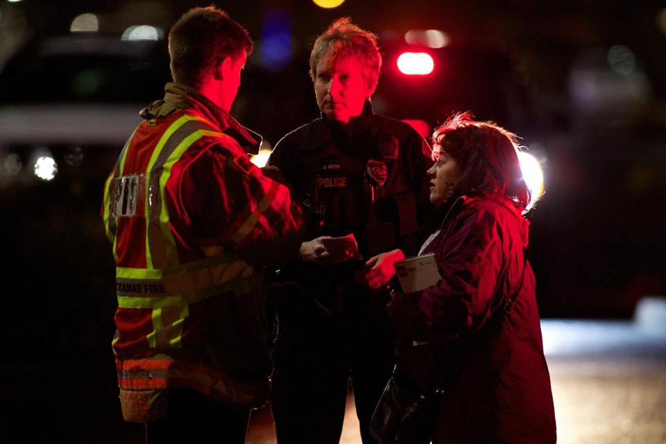 A firefighter and police officer spoke to a woman outside Clackamas Town Center on Tuesday. Police said the shooter had died, apparently of a self-inflicted gunshot wound.