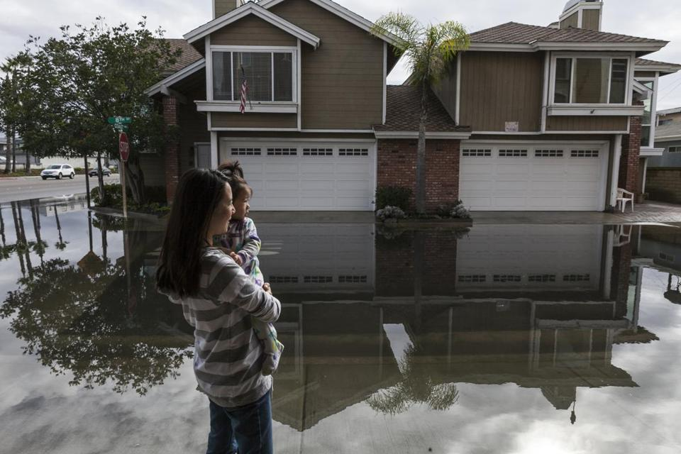 Juliana Chen of Huntington Beach, Calif., stepped out of her house to survey flooding caused by extremely high tides in the Sunset Beach area near the Pacific Coast Highway on Thursday.