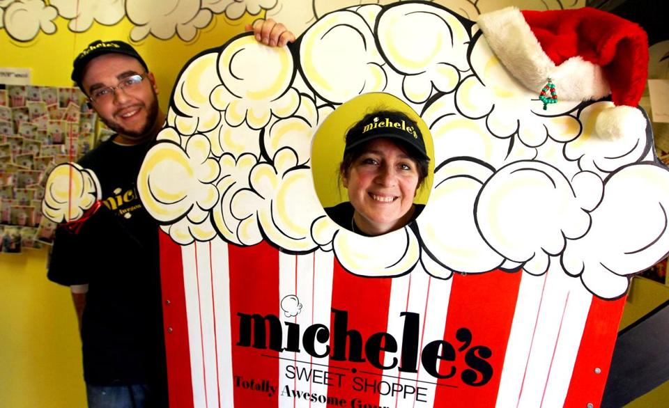 Culinary chef Jesse LaMontagne, left, with his mom, Michele Holbrook, right, posed for a picture in the 'Poparazzi' popcorn bucket set up for customers to take fun pictures, inside her business, Michele's Sweet Shoppe in Epsom, N.H.