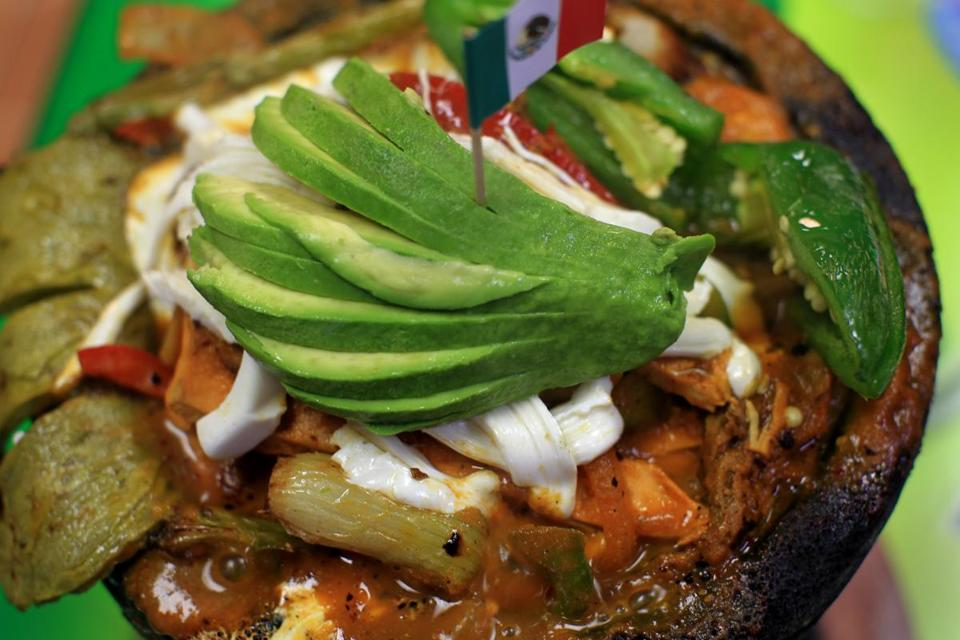 Molcajete for two includes sizzling meat, seafood, cheese, and cactus.