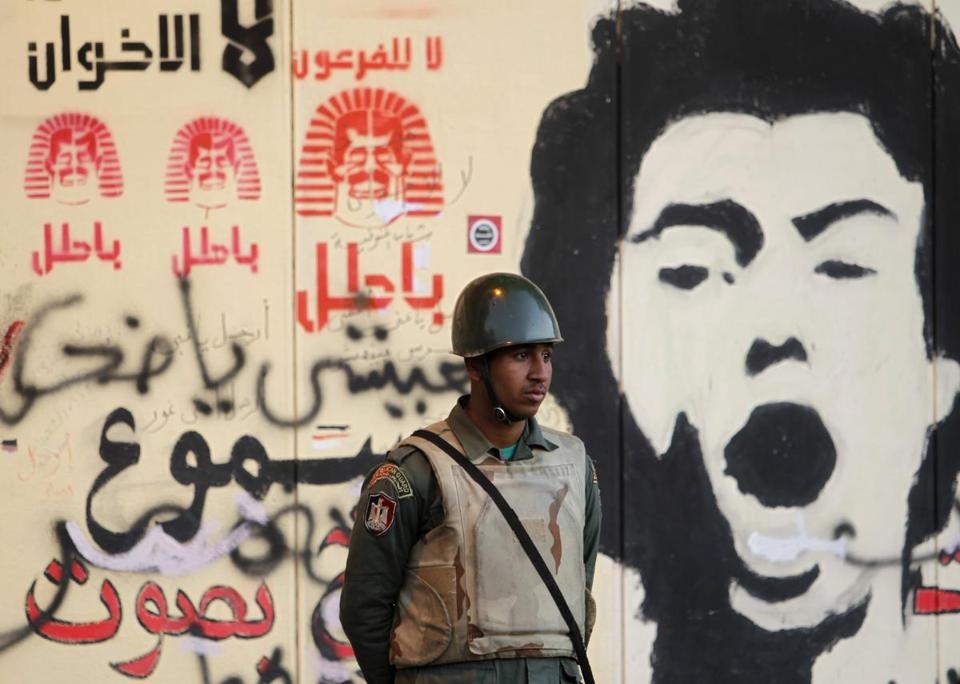 A soldier stood outside the presidential palace in Cairo, where protesters slogans were peppered on a wall.