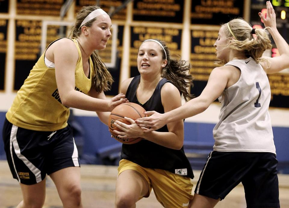 Devon Caveney drives between Emma Bentley (left) and Rachel Cormier during practice.