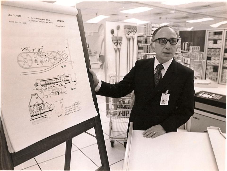 Mr. Woodland with a diagram of a supermarket check-out station in 1974 at an IBM laboratory in Raleigh, N.C.