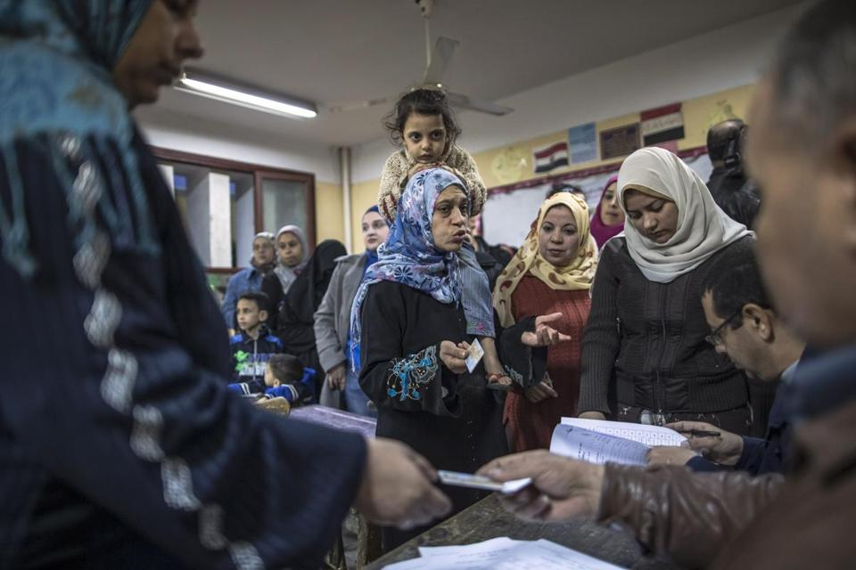 A woman carrying her daughter complained to electoral staff at a polling station in Cairo on Saturday.