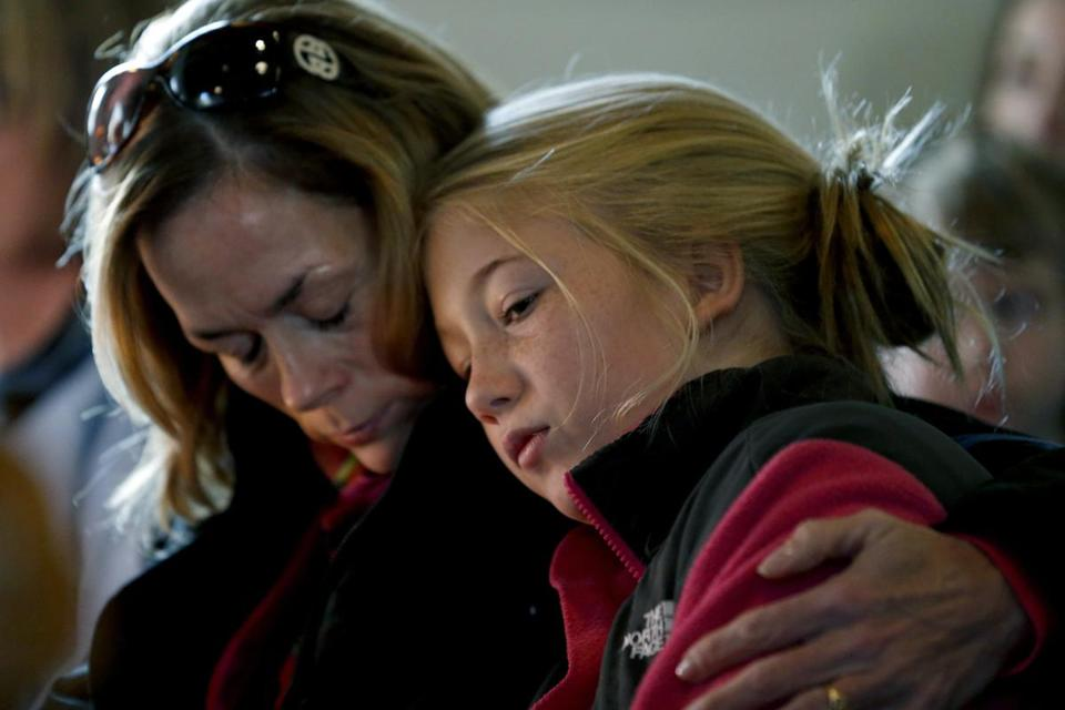 Molly Delaney (left) comforted her 11-year-old daughter, Milly, during a service in honor of the victims.