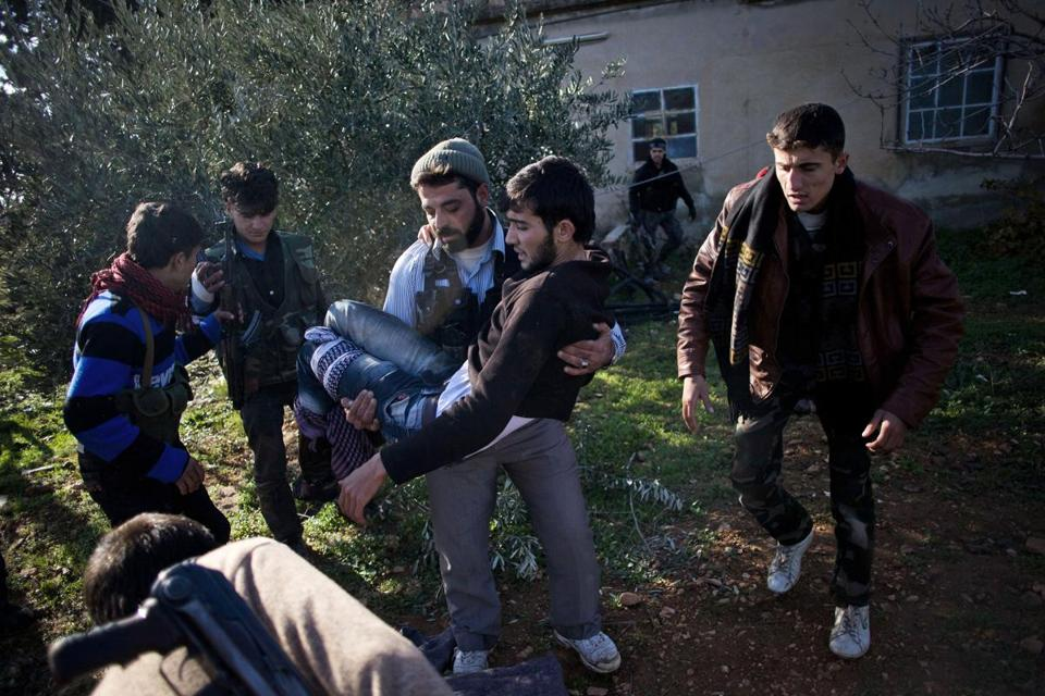 A Free Syrian Army fighter carried an injured comrade during an assault on a military base in Tal Sheen, Syria. Fighting continued around the country on Saturday.