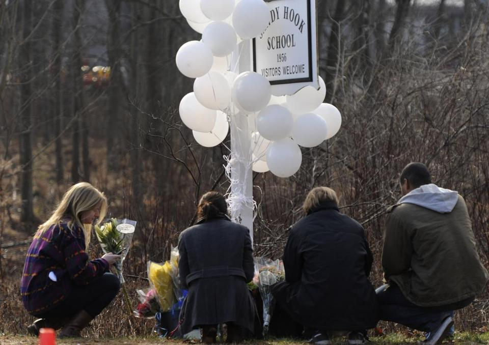 A group of teenagers placed some flowers beneath the school sign at the entrance to Sandy Hook School in Newtown, Conn., one day after the shootings.