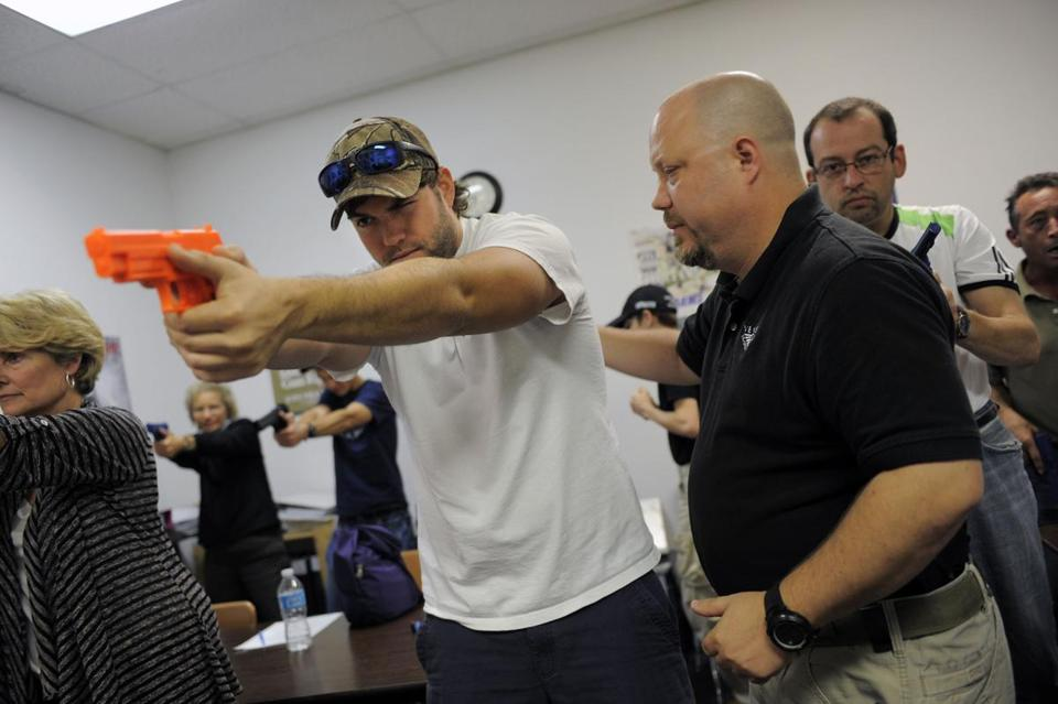 Instructor Mike Magowan worked with students during a concealed weapons permit class in Florida on Saturday.