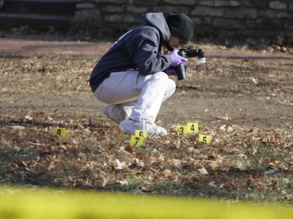 A law enforcement officer took photos of evidence gathered outside a Topeka, Kan., home where a man suspected of fatally shooting two officers was shot dead by police.