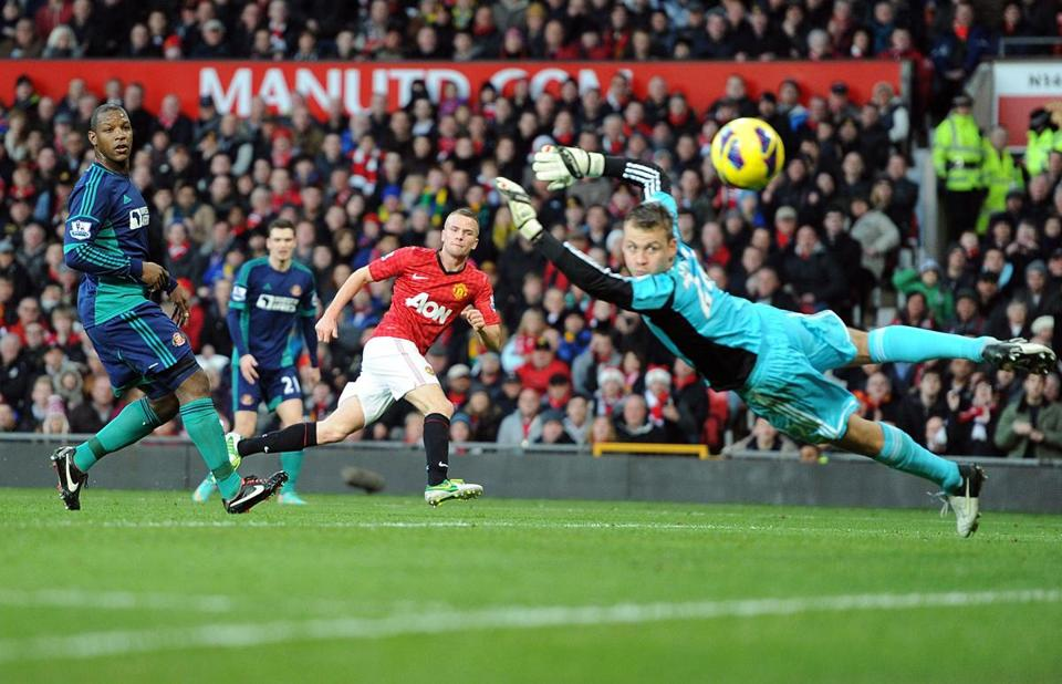 Manchester United's Tom Cleverley, center in red, scores past Sunderland goalkeeper Simon Mignolet during the English Premier League soccer match at Old Trafford, a storied soccer venue that rivals Gillette Stadium in its appeal for devout fans.
