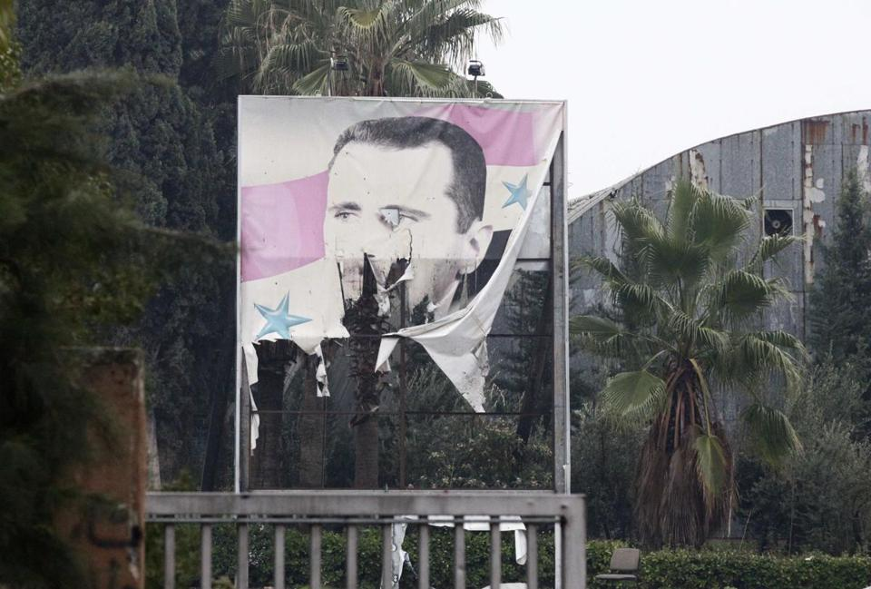 A poster of President Bashar Assad of Syria was torn at the entrance of a factory in Ouwayjah village in Aleppo. Opposition forces are moving closer to Damascus.