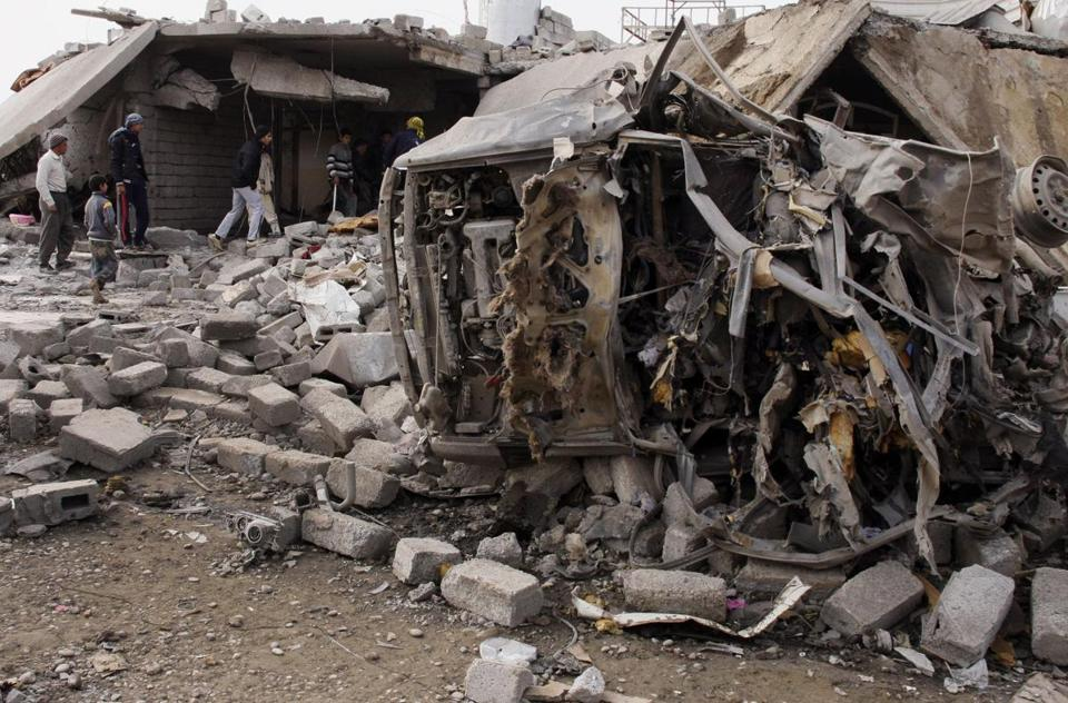 Iraqis inspected the scene of a car bomb attack Monday in al-Mouafaqiyah, near Mosul. Seven people were killed.