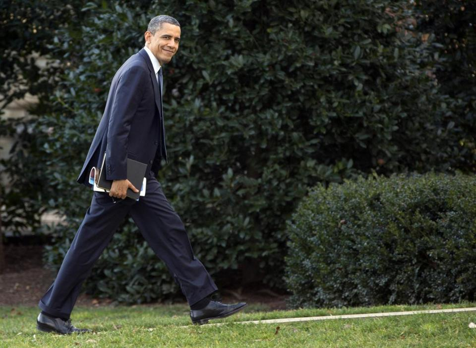 President Barack Obama looked to the media as he walks to the Oval Office of the White House as he returns from greeting members of the staff, Tuesday, Dec. 18, 2012, in Washington.