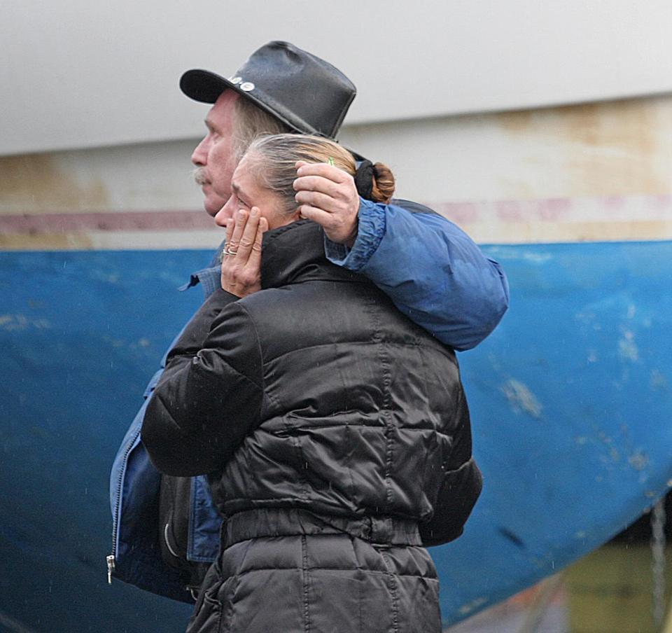 Dave and Karyn Walsh consoled each other as they looked at their boat Naut Again that was destroyed in a suspicious fire Wednesday night at the Taylor Marina in Marshfield.
