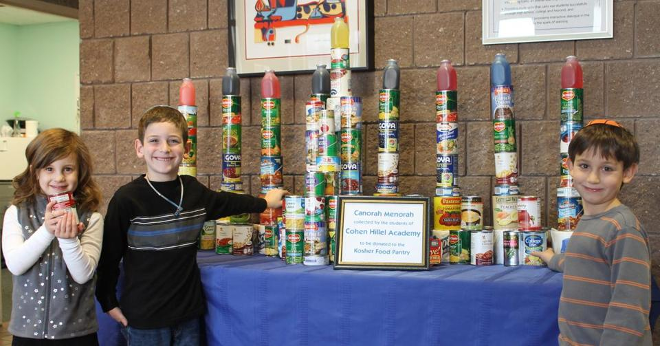 Cohen Hillel Academy in Marblehead made a Hanukkah menorah of food for the hungry. From left, Chloe Stux of Lynn, Ely Wallen of Swampscott, Ezra Myerson of Marblehead.