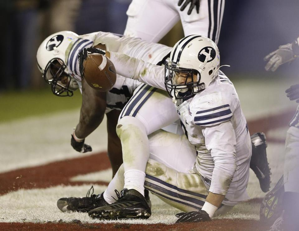 Brigham Young linebacker Kyle Van Noy scored on a recovered fumble which he caused when he hit San Diego State quarterback Adam Dingwell in the end zone during the fourth quarter of the Poinsettia Bowl NCAA college football game Thursday, Dec. 20, 2012, in San Diego.