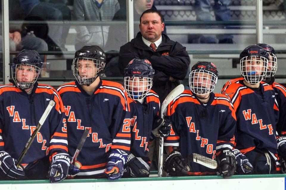 Walpole head coach Ron Dowd stood behind his team during a hockey game against Wellesley High on Saturday.