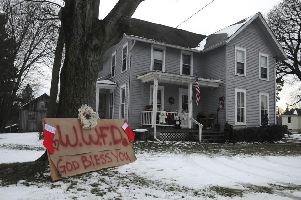 A makeshift memorial paying tribute to firefighters sat in front of a house after three people were killed on Monday.